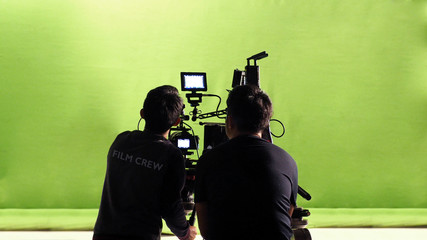 Behind the scenes of TV commercial movie film or video shooting production which crew team and photographer camera man setting up green screen for chroma key technique in big studio.