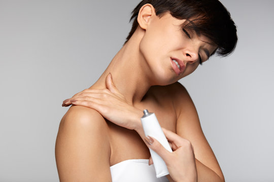 Injury Treatment. Beautiful Woman With Neck Pain Applies Cream