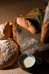 Bakery products with floured bread, loaf, baguette and a cup of milk