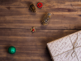 Vintage gift box, fir cones with Christmas toy on wood background with copy space for text. Top view, Studio photography