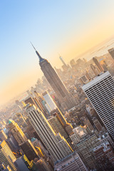 Wall Mural - New York City. Manhattan downtown skyline with illuminated Empire State Building and skyscrapers at sunset seen from Top of the Rock observation deck. Vertical composition.
