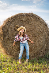Cute Child having fun outdoors, little girl cowboy playing in wheat field at sunset. Happy baby girl with toy gun and cowboy hat enjoying nature. American Cowgirl. lovely smiling toddler portrait.