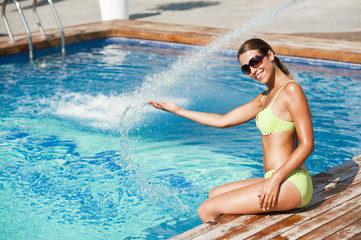 Young, pretty woman on summer holiday at pool (model-released)