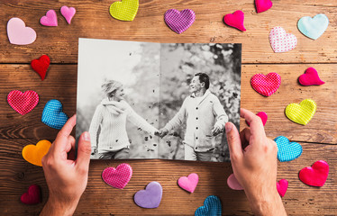 Hands holding picture of senior couple, colorful hearts. Studio