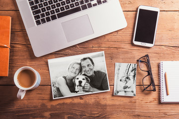 Office desk. Objects and black-and-white photos of senior couple