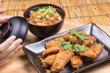 Fried chicken wings served with fry rice