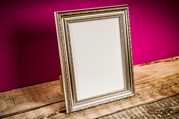 old and wooden shelf with frame and purple wall