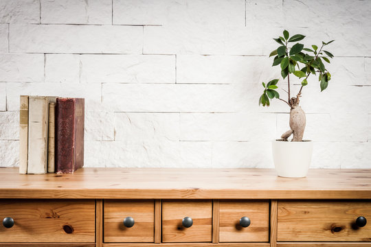 shelf with a book and flower and a white brick wall