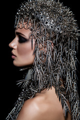 High fashion beauty model with metallic headwear and dark makeup and blue eyes on black background
