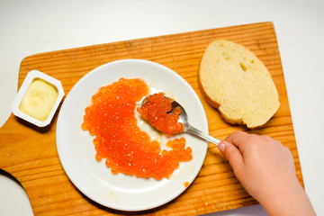 Child hand eating red caviar with spoon on white background. Close up image of delicacy food luxury lifestyle
