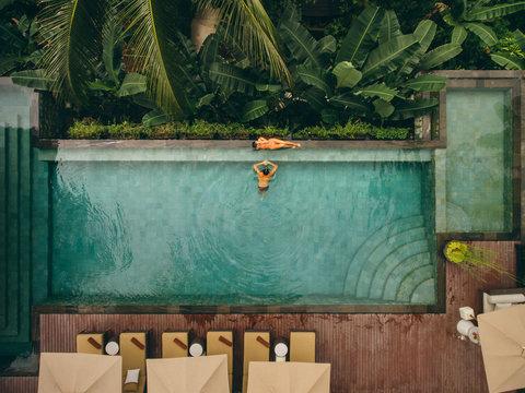 Couple relaxing at tropical resort swimming pool