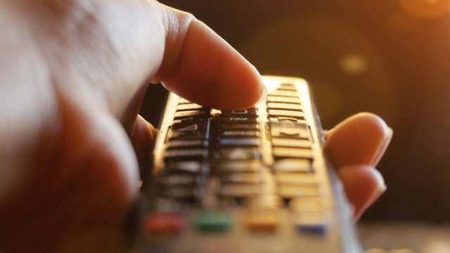 Close up of woman's hand with a television remote control changing channels at sunset time  lense flare effects