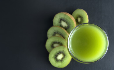 Kiwi Juice and kiwi fruit arranged on black background.