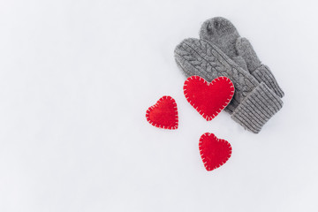Girl in mittens holding heart on Valentine's day in winter outdoors