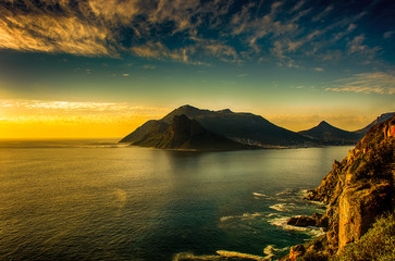 South Africa Hout Bay Cape Town golden hour scenic, peaceful and romantic panoramic landscape and seascape with a golden sunset over a blue quiet sea with mountains and a blue sky with clouds