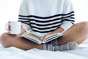 Beautiful young woman reading a book on the bed.