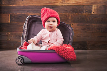 Cute baby in pink travel bag