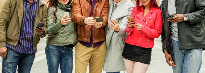 Happy multi ethnic friends using mobile phones