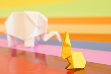 Paper origami elephant isolated on a colorful background