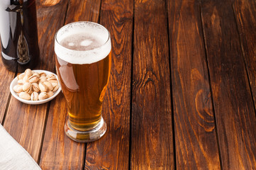 glass of light cold frothy beer, nuts, bottle, old wooden table