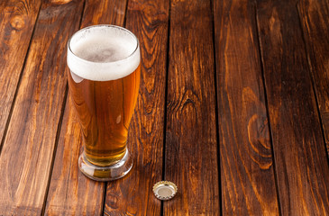 glass of light cold frothy beer,cap old wooden table
