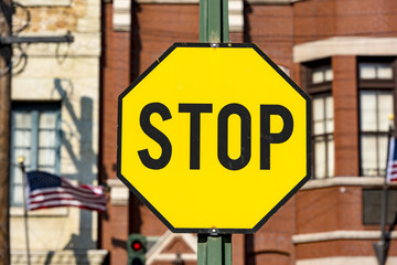 STOP -road sign with black latters on the yellow background in USA