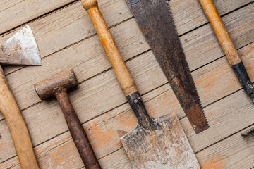 Old rustic tools on wooden texture background. Flat lay with ax, sledgehammer, shovel, saw, rake. Top view close-up