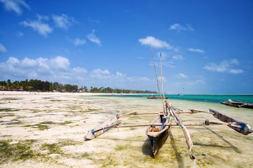 Wall Mural - Beach at low tide with traditional dhow boat in Zanzibar