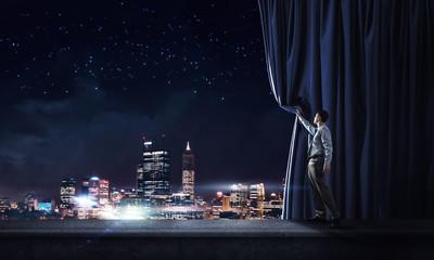 Night city behind curtain