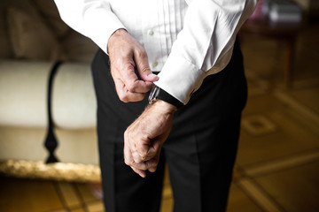Old groom fixes his sleeves over watch on his wirst