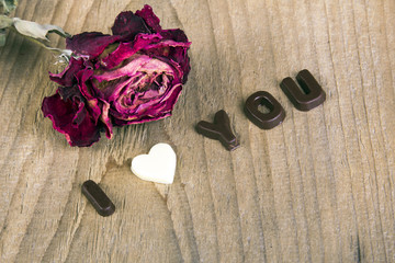 dried rose and chocolate words I LOVE YOU on wooden background