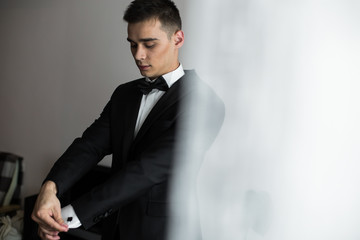 Handsome young man in black suit fixes his sleeves under the jac