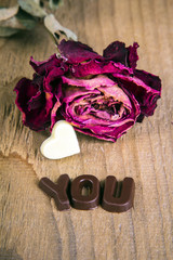 dried rose and chocolate word YOU on wooden background