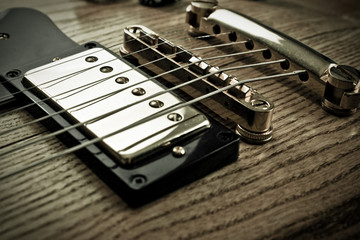 Golden pick-up, bridge and metallic strings of an electric guitar. Close up picture taken in studio.