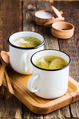 Homemade simple chicken soup in white mug