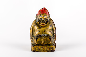 Cast iron antique billiken coin bank on a white background