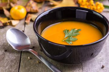 Autumn pumpkin soup in black bowl on natural desk.