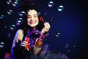 fashion model with creative make-up blowing soap bubbles.