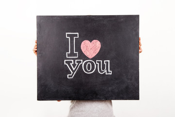 hands holding black сhalkboard with text I love you