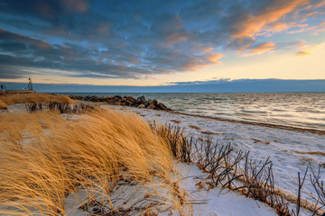 Grass, white sand dunes beach and sky at sunset on the shore of the Baltic Sea. Poland.