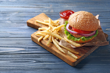 Tasty burger with french fries on cutting board