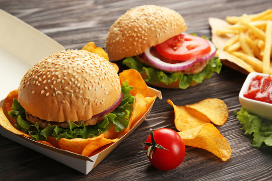 Tasty burger with french fries and chips on table