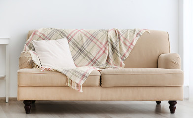 New cozy couch with pillow on light wall background
