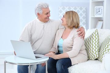 Grandparents using laptop at home