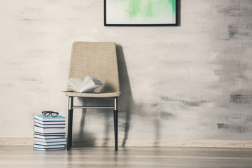 Chair with books on gray wall background
