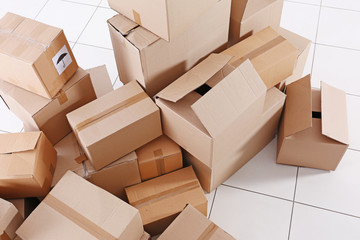 House move concept. Carton boxes on tile floor background
