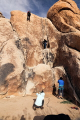 Two young women rock climb in the desert while other people assist and take photos