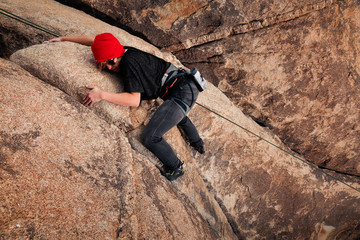 Young caucasian woman dressed for cold weather rock climbing in the desert climbs a cliff. Wearing a red hat, jeans, and sunglasses