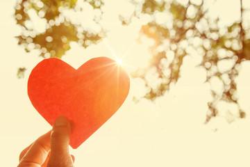 Hand holding paper heart.  Instagram effect.