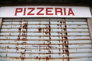 the big sign of Pizzeria with the gate closed